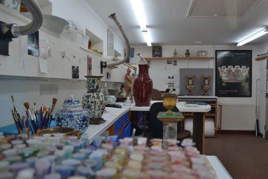 An artisan and artists studio with vases, fume extraction, paints. A colourful scene.
